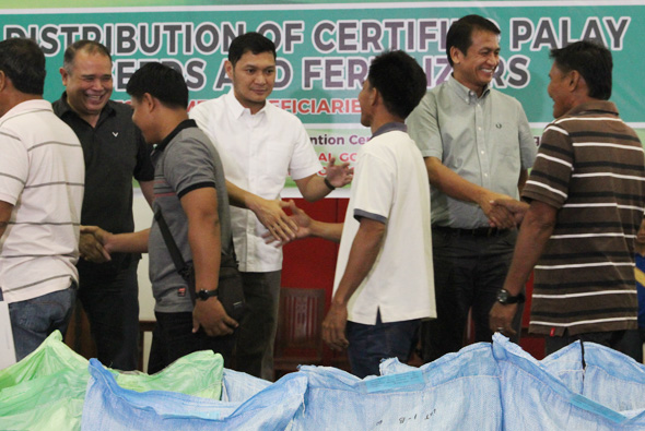 Governor Amado Espino III, Vice Governor Ferdinand Calimlim and Alaminos City Mayor Arthur Celeste lead the distribution of bags of certified palay seeds and fertilizers to district 1 farmers
