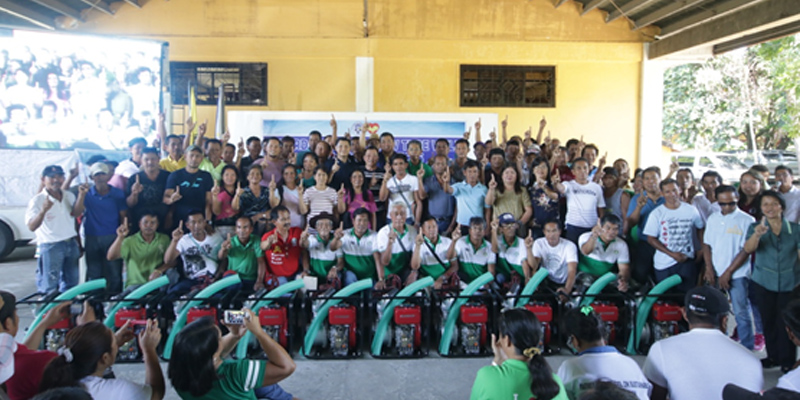 Representatives of the seventy-seven farmers' and irrigators' associations who received a total of 80 units of shallow tube wells flash the Pangasinan No. 1 sign with Governor Amado I. Espino.